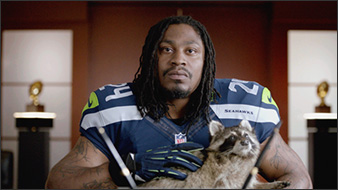Marshawn Lynch holds a raccoon and lovingly strokes its fur.