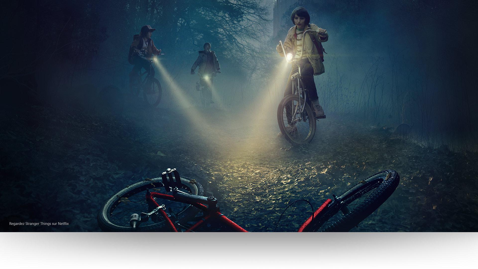 StrangerThings - Dustin, Lucas et Mike éclairent un vélo abandonné sur un sentier forestier lugubre.